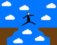 Businessman jumping over the precipice. Overcomes difficulties Royalty Free Stock Photo