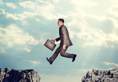 Businessman jumping over precipice Royalty Free Stock Images