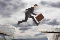 Businessman jumping over rocks Stock Photos