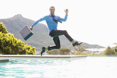 Businessman jumping over swimming pool Royalty Free Stock Photo