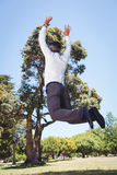 Businessman jumping in the park Stock Images