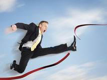 Businessman Jumping Through Red Tape Royalty Free Stock Photo