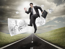 Businessman jumping on a road with drawings floating Stock Photo
