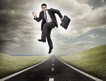 Businessman jumping on a road Stock Image