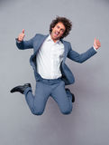 Businessman jumping and showing thumbs up Stock Images