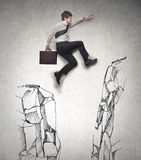Businessman jumping. And trying to reach a higher mountain Royalty Free Stock Photography