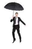Businessman jumping with an umbrella Royalty Free Stock Image