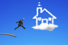 Businessman jumping from wooden board to house shape cloud Stock Images