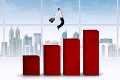 Businessman jumps above chart Stock Images