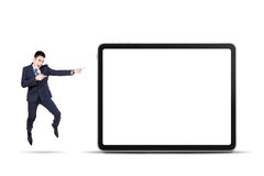Businessman jumps and pointing digital tablet Royalty Free Stock Image