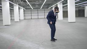 A businessman jumps while wearing VR headset in an office. 4K stock video