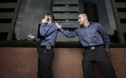Businessman karate chopping another businessman stock photos