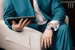 Businessman keep a digital tablet in hand whilst sitting on a sofa in a blue suit. on hand expensive mechanical watch Stock Photos