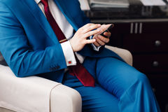 Businessman keep a phone in hand whilst sitting on a sofa in a blue suit. on hand expensive mechanical watch with Royalty Free Stock Photography