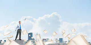 Study hard to become successful businessman. Businessman keeping hand with book up while standing among flying books with cloudly sky on background. Mixed media Royalty Free Stock Photography