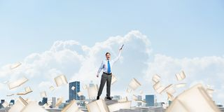 Study hard to become successful businessman. Businessman keeping hand with book up while standing among flying books with cloudly sky on background. Mixed media Royalty Free Stock Images