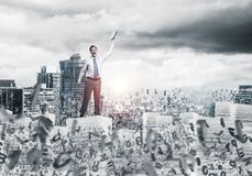 Study hard to become successful businessman. Businessman keeping hand with book up while standing among flying letters with cityscape and sunlight on background Royalty Free Stock Photography