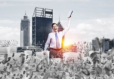 Study hard to become successful businessman. Businessman keeping hand with book up while standing among flying letters with cityscape and sunlight on background Royalty Free Stock Images