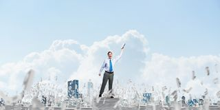 Study hard to become successful businessman. Businessman keeping hand with book up while standing among flying letters with cloudly sky on background. Mixed Royalty Free Stock Photo