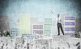 Study hard to become successful businessman. Businessman keeping hand with book up while standing among flying letters with drawn cityscape on background. Mixed Stock Photography