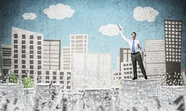 Study hard to become successful businessman. Businessman keeping hand with book up while standing among flying letters with drawn cityscape on background. Mixed Royalty Free Stock Photography