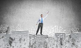 Study hard to become successful businessman. Businessman keeping hand with book up while standing among flying letters with grey background. Mixed media Stock Images