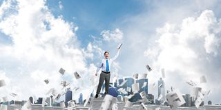 Study hard to become successful businessman. Businessman keeping hand with book up while standing among flying paper documents with cloudly sky on background Royalty Free Stock Photos