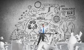 Study hard to become successful businessman. Businessman keeping hand with book up while standing among flying papers with eco-analytical information on Royalty Free Stock Photos