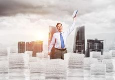 Study hard to become successful businessman. Businessman keeping hand with book up while standing on pile of paper documents with cityscape and sunlight on Royalty Free Stock Images