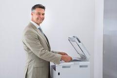 Businessman Keeping Paper On Photocopy Machine In Office. Side view of businessman keeping paper on photocopy machine in office Stock Photos