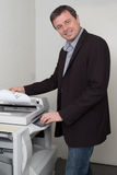 Businessman keeping paper on photocopy machine. Side view of businessman keeping paper on photocopy machine in office Stock Photography