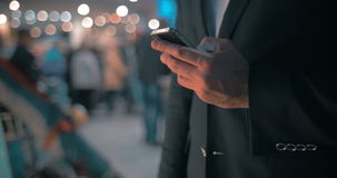 Businessman keeping in touch. Businessman with smart phone at the airport. He typing sms or email on touchscreen. Defocused crowd in background stock video