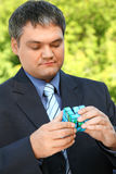 Businessman keeps in hand cube outdoor in summer Royalty Free Stock Image