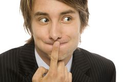 Businessman keeps a secert. Businessman holds his finger to his lips to keep a secret Royalty Free Stock Image