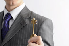 Businessman with a key. This businessman knows  the key to the mystery of achieving the well-being Royalty Free Stock Images