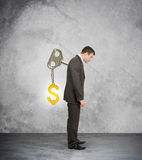 Businessman with key in back and gold dollar sign Royalty Free Stock Image