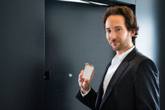 Businessman with key card for room door in hotel. Young business man standing with a keycard in front of a room door in a hotel Royalty Free Stock Image