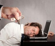 Businessman with a key winder on his back. Sleeping on laptop Stock Photography