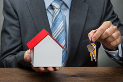 Businessman with keys and house model Royalty Free Stock Photography