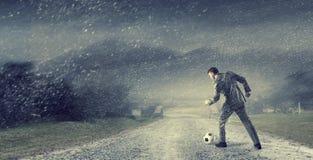 Businessman kicking ball . Mixed media Stock Photo