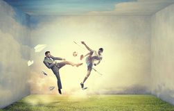 Businessman kicking ball. Young businessman in suit playing football outdoors Royalty Free Stock Photos