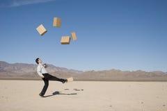 Businessman kicking boxes Stock Photos
