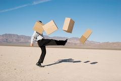Businessman kicking boxes Royalty Free Stock Image