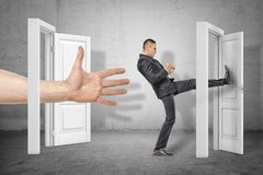 Businessman kicking a door and big hand appearing out of an open door on grey wall background. Business and management. Way to success. Taking chances royalty free stock image