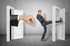 Businessman kicking door and big stretched fist appearing out of open door on grey wall background. Business and management. Way to success. Taking chances stock images