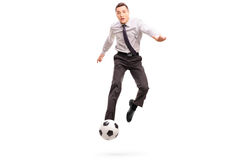 Businessman kicking a football shot in mid–air Stock Images