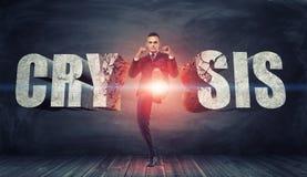 Businessman kicks and destroys concrete letters 'Crisis' with confident face expression. Stock Photo