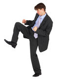 Businessman kicks down on white background Stock Photo