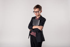 Businessman kid holding laptop in his hands. Young cute businessman in a suit and eyeglasses holding laptop in his hands Royalty Free Stock Images
