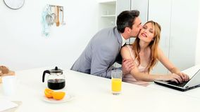 Businessman kissing his blond wife in the morning stock video